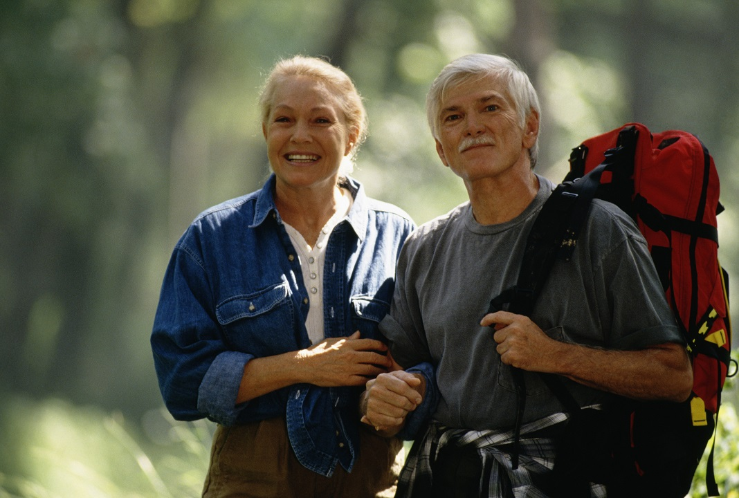 Elderly couple hiking in the woods in one of the best places to retire on the West Coast.